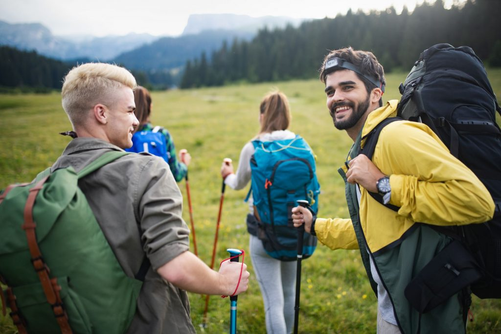Hiking with friends is so fun. Group of young people with backpacks walking together and looking happy