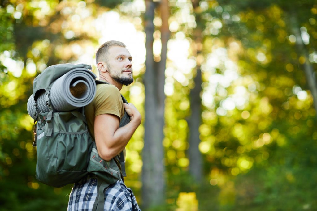 Young man with backpack walking in the forest while searching for goos place for settle